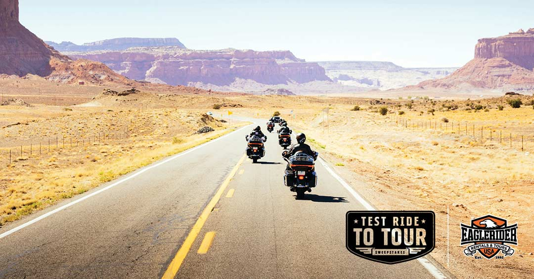 A group of motorcycles ride off into the distance on a desert highway.