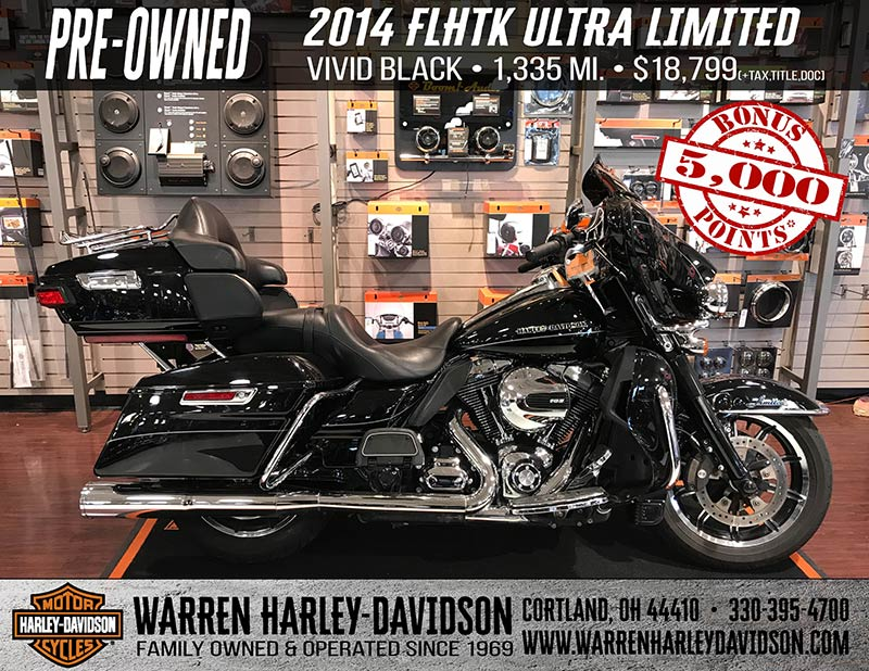 A black 2014 FLHTK Ultra Limited is parked in the showroom.