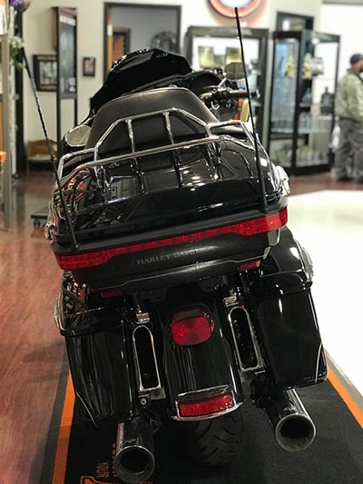 A rear view of a black and white motorcycle parked in the showroom.