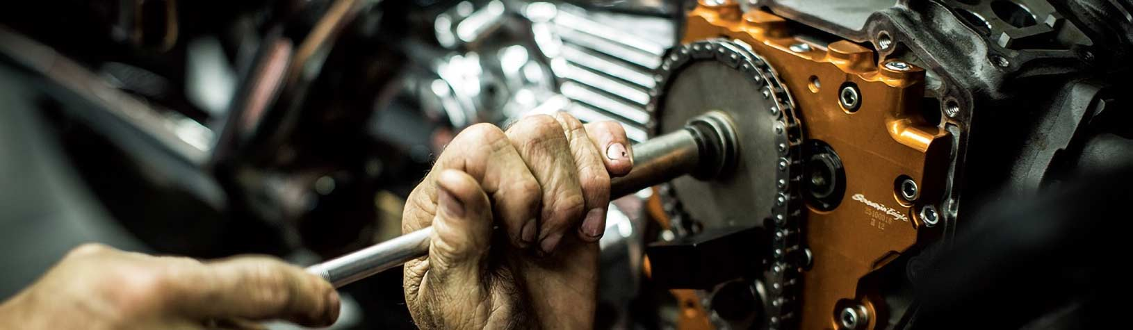 A closeup of a hand turning a tool on an engine.