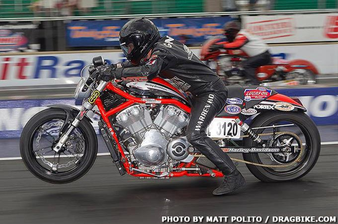 A rider leans forward on his racing bike as the front tire rises off the ground.