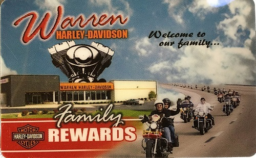 A retro-looking print-photo of the dealership storefront with riders waving as they ride by.
